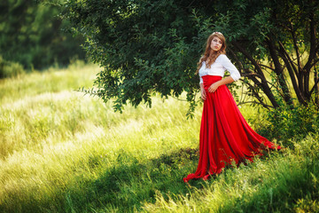 woman wearing red skirt standing under the tree