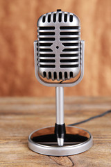 Vintage microphone on table on brown background
