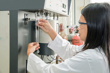 Scientist using chemical machine(autosorb) in laboratory