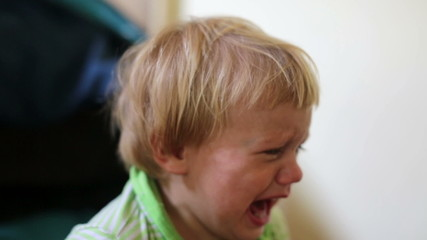 Crying two year old baby in buggy