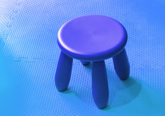 Small blue plastic stool for kids isolated on cryans soft floor