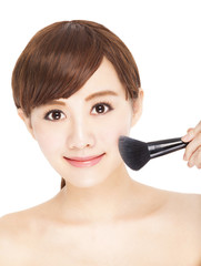 pretty young woman using brushes makeup her face