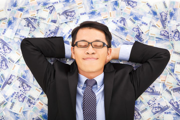 business man enjoying and lying on the stacks of money