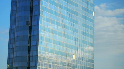 Moving clouds reflected in the glass wall of a skyscraper