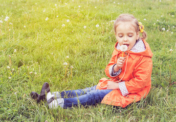 girl on grass with dandelion