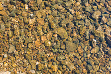 many stones under clean transparent water of river