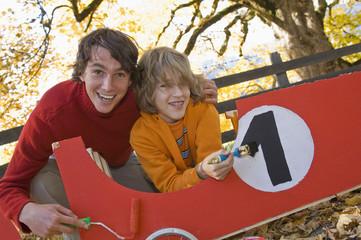 Mann und Junge malen Seifenkiste
