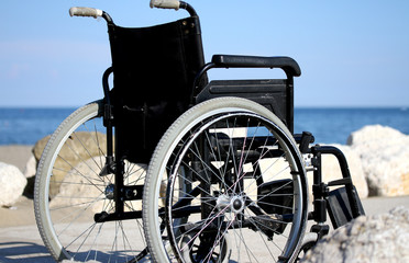 wheelchair on the rocks of the blue sea in summer