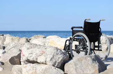 black wheelchair on blue ocean shore in a sunny summer day