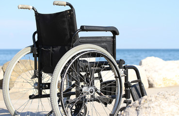 black wheelchair on the rocks of the sea