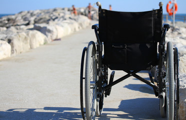 wheelchair from behind near the shore of the sea