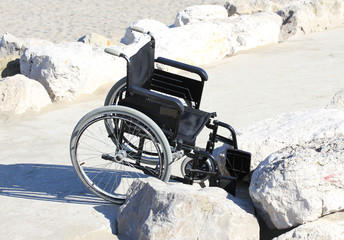 wheelchair stuck on the rocks by the sea