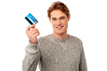 Smiling young man holding credit card