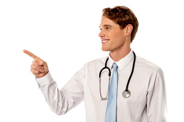 Smiling male physician pointing away