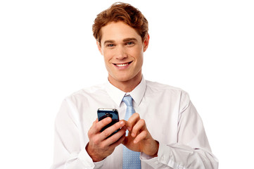 Smiling business executive using mobile phone