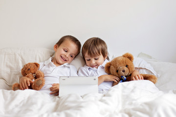 Two cute boys, sitting in bed, playing with tablet, teddy bears