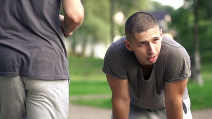 Tired man resting during jogging in park, super slow motion