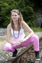 Jeune fille branchée posant sur des rails