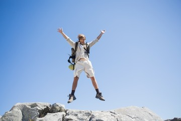 Handsome hiker jumping at the summit smiling at camera