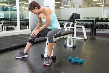 Fit brunette sitting on bench holding injured knee