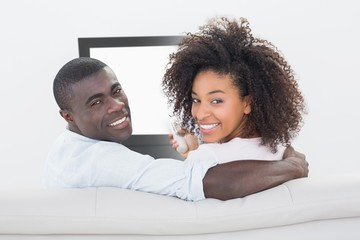 Couple sitting on couch together watching tv