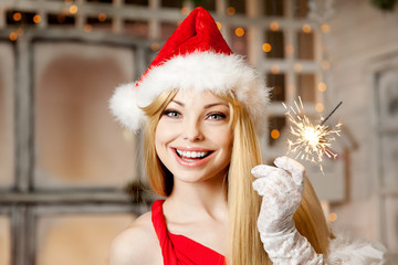 Young beauty santa woman near the Christmas tree. Fashionable lu