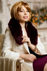 Beautiful adult woman in a winter coat with fur. Trendy modern b