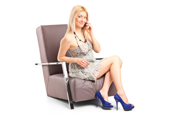 Woman talking on phone seated in an armchair
