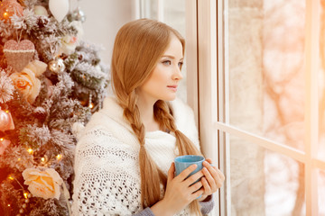 Beautiful young woman drinking tea at the Christmas tree. Beauti