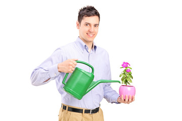 Man holding plant and a watering can