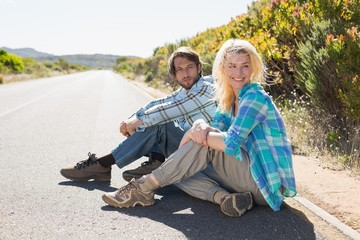 Attractive couple sitting on the road