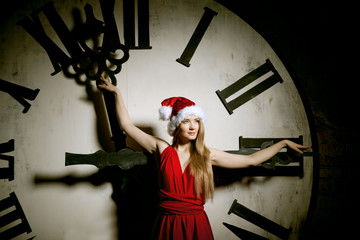 Luxury young woman in Santa costume on the big dial. Girl and cl