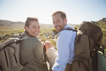 Hiking couple sitting on mountain terrain smiling at camera