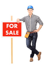 Male repairman leaning on a for sale sign