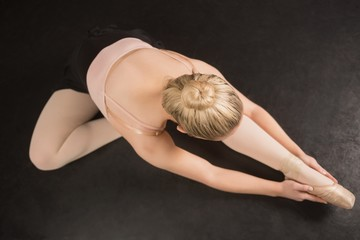 Ballerina sitting and bending forward