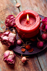 Red candle with dry rose