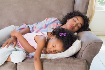 Pretty mother sleeping with her daughter on the couch