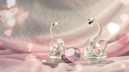 Crystal or glass swans with a diamond on pink cloth