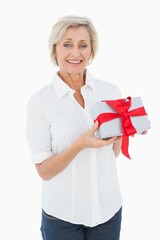Mature blonde smiling at camera holding gift