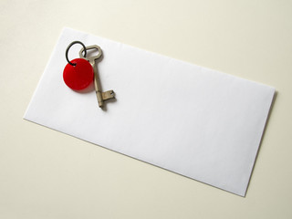 Real old key on real envelope on real cream color table with rea