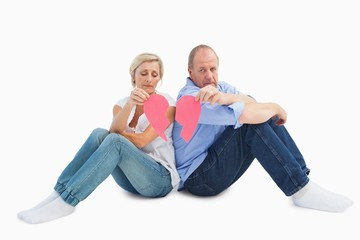 Sad mature couple holding a broken heart