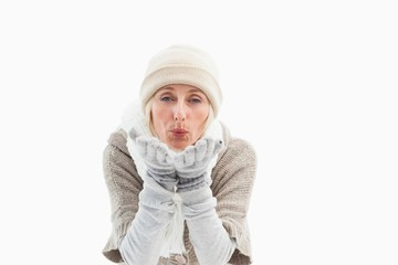 Mature woman in winter clothes blowing kiss