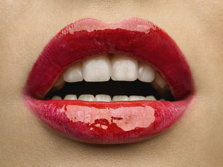 Close-up of woman's lips with bright fashion red glossy makeup.