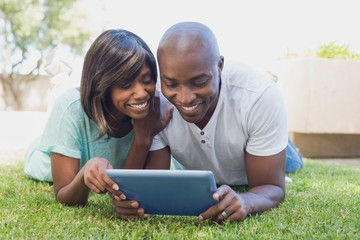Happy couple lying in garden using tablet pc together