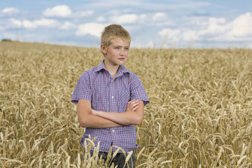 Portrait of the beautiful boy in wheat