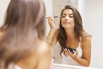 Pretty woman applying eyeshadow in front of a mirror
