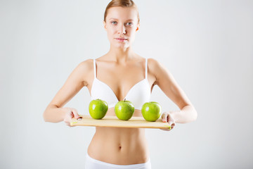 Girl with green apples in lingerie. concept of healthy eating