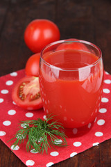 Tomato juice in glass, on wooden background