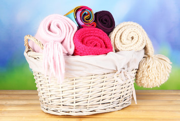 Warm knitted scarves in basket