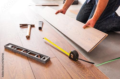 Leinwanddruck Bild Man installing new laminated wooden floor